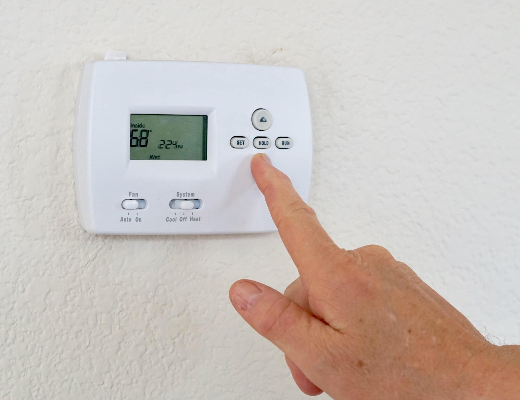 Adult male hand with finger pointed on a thermostat