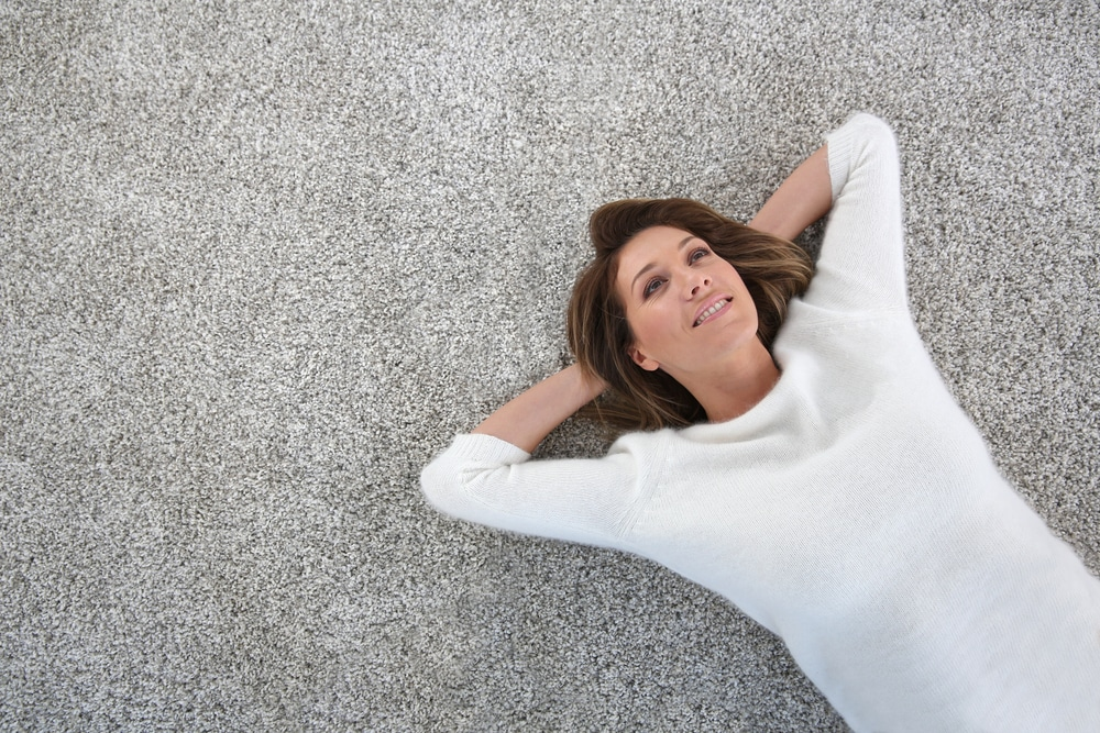 Upper view of woman relaxing on carpet at home after having carpets professionally cleaned