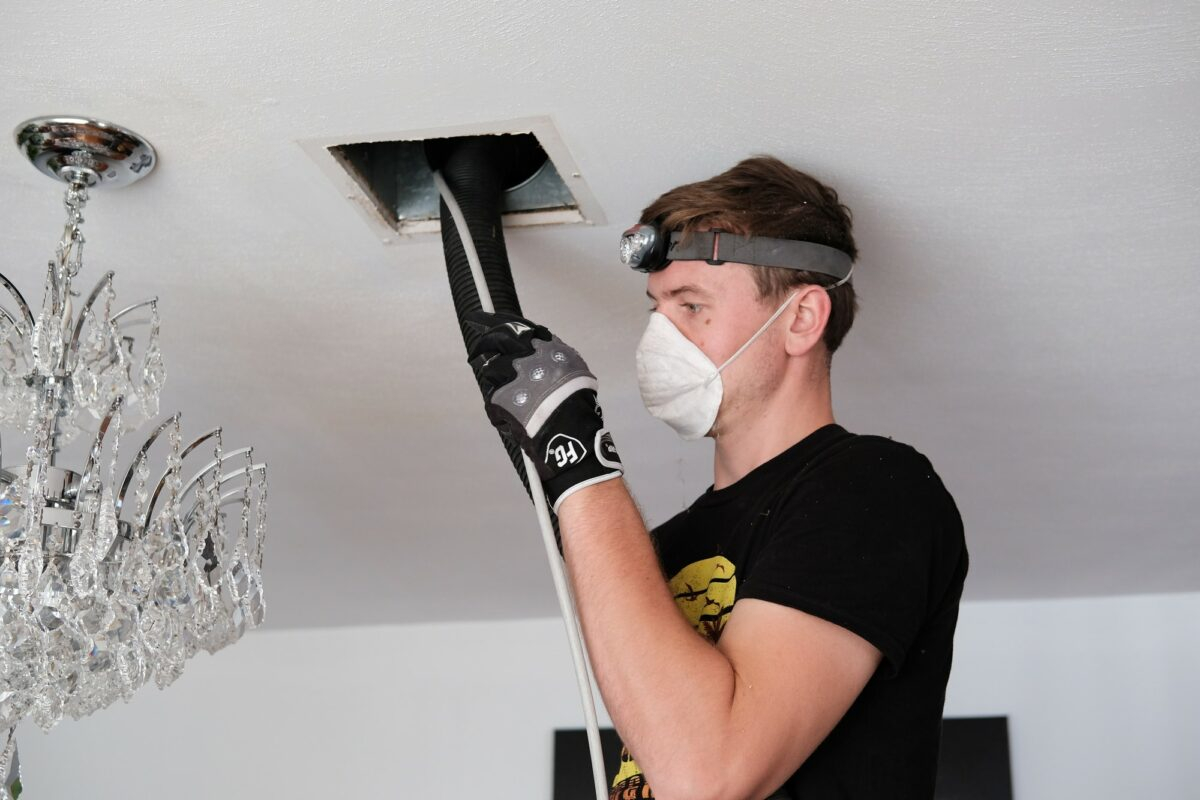man cleaning an air duct in the ceiling